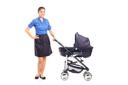 madre soltera: Retrato de cuerpo entero de una joven madre que presenta al lado de un cochecito de bebé aislado en el fondo blanco