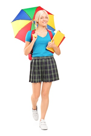 Full length portrait of a blond female student walking with umbrella and books isolated on white background photo