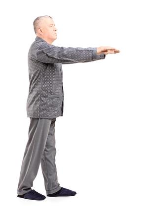 sleepwalking: Full length portrait of a mature man in pajamas sleepwalking isolated on white background