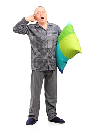 yawn: Full length portrait of a sleepy mature man in pajamas holding a pillow isolated on white background Stock Photo