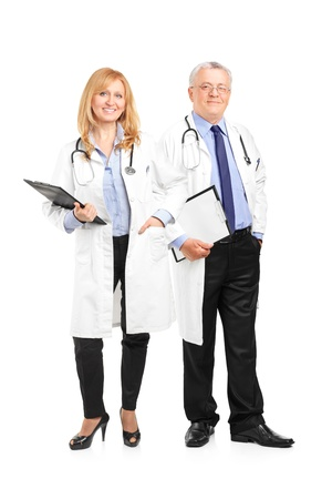 Full length portrait of a team of doctors holding a clipboard and posing isolated on white background photo