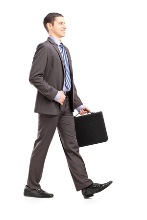 full suit: Full length portrait of a young businessman with briefcase walking isolated on white background Stock Photo