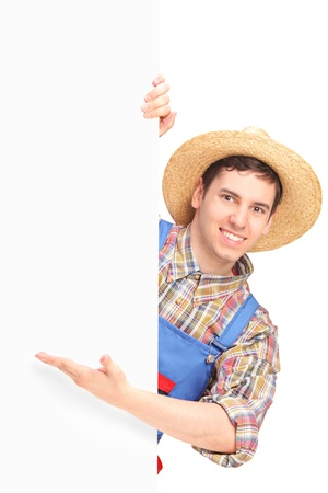 Young smiling farmer gesturing on a blank panel isolated on white background photo
