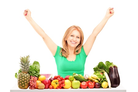 Happy woman with raised hands posing with pile of fruits and vegetables isolated on white background photo