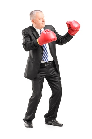 full suit: Full length portrait of a mature businessman with red boxing gloves ready to fight isolated on white background