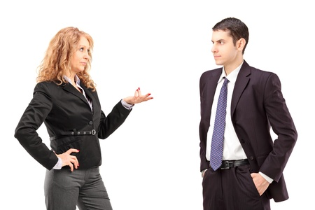 disagreeing: Mature female in a formal wear having a conversation with a young male colleague isolated against white background