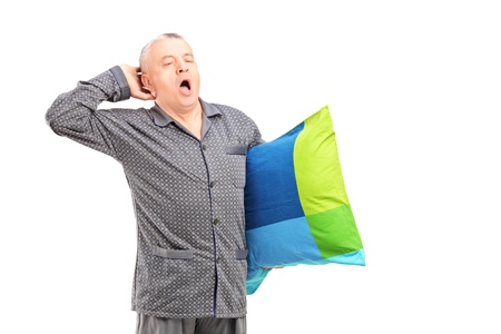 late 50s: A sleepy mature man in pajamas holding a pillow and yawning isolated on white background Stock Photo