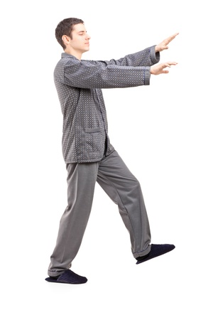 sleepwalking: Full length portrait of a young man in pajamas sleepwalking isolated on white background