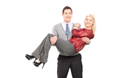 Happy young man carrying his girlfriend in his arms isolated on white background photo
