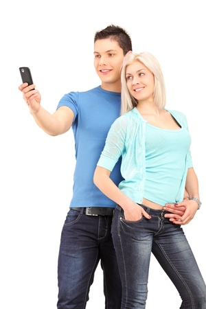 Attractive young couple taking a photo with a mobile phone, isolated on white background photo