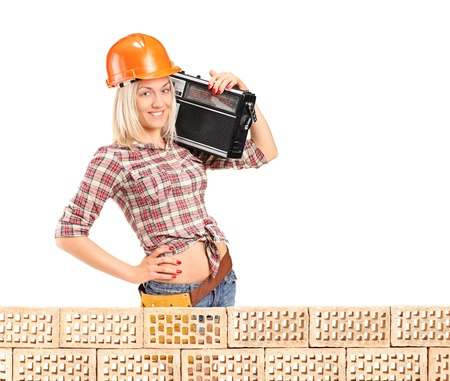 sexy construction worker: Female construction worker with radio posing next to a pile od bricks isolated on white background