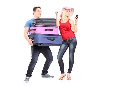 pareja enojada: Hombre frustrado joven que lleva equipaje de su novia mientras que ella está haciendo una llamada