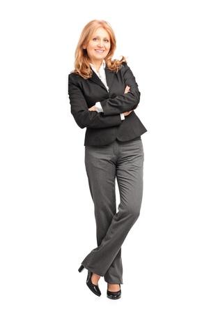 businesswoman suit: Retrato de cuerpo entero de una mujer de negocios sonriente apoyado en la pared aislado sobre fondo blanco Foto de archivo