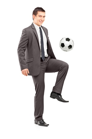 Full length portrait of a young handsome businessman kicking a football isolated on white background photo