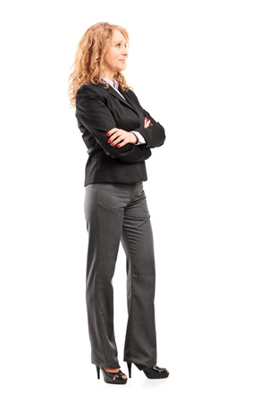 serious woman: Full length portrait of a businesswoman standing with folded arms isolated on white background