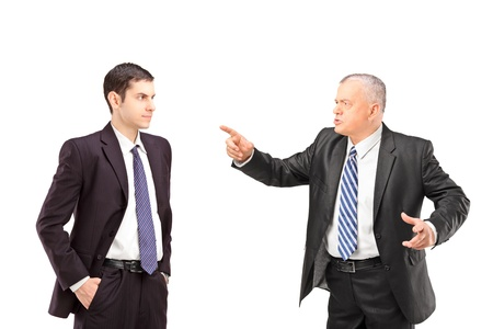 disagreeing: Angry mature man in a suit pointing with a finger towards a young man in a suit isolated on white background Stock Photo
