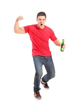 hombre tomando cerveza: Retrato de cuerpo entero de un ventilador eufórica celebración de una botella de cerveza y vítores aislados en fondo blanco