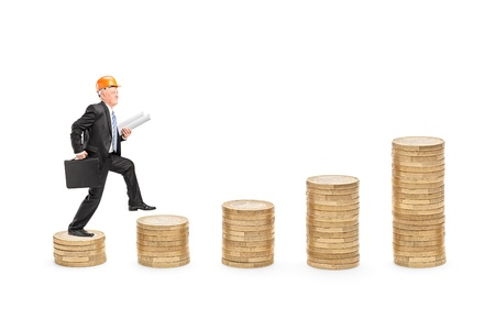 Full length portrait of a male engineer with blueprints walking over piles of coins isolated on white background photo