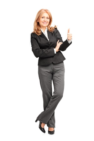 Full length portrait of a smiling businesswoman leaning on wall and giving a thumb up isolated on white background photo