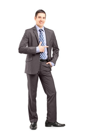 Full length portrait of a young businessman standing and pointing isolated on white background photo