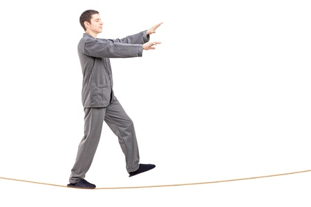 sleepwalker: Full length portrait of a young man in pajamas sleepwalking on a rope isolated on white background