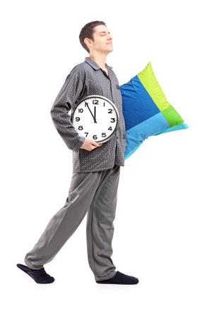 pijama: Retrato de cuerpo entero de un hombre joven con una almohada y un reloj sonambulismo aislado sobre fondo blanco