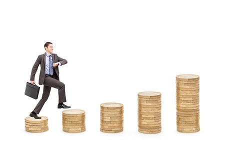 pile of coins: Full length portrait of an ambitious businessman with a briefcase walking over piles of coins isolated on white background