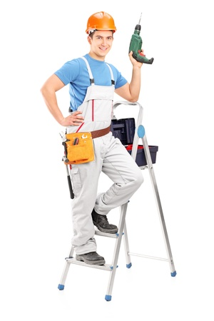 Full length portrait of a repairman with a hand drilling machine standing on a ladder isolated on white background photo
