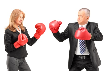Mature businesswoman with boxing gloves having a fight with a businessman isolated on white background photo
