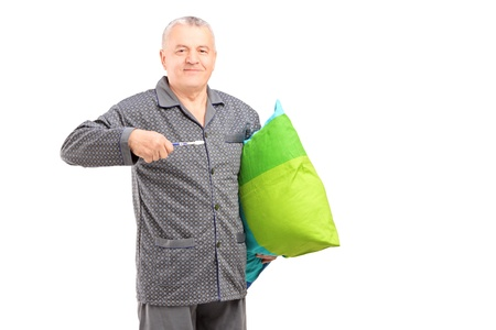 dentalcare: Mature man in pajamas holding a tooth brush and a pillow isolated on white background