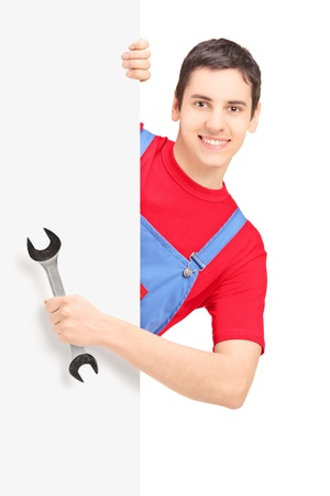 Repairman holding a wrench and posing behind a blank panel isolated on white background photo