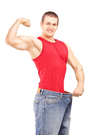 lose weight: Weight loss man in an old pair of jeans showing his muscular body isolated on white background Stock Photo