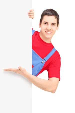 A smiling repairman showing on a blank panel isolated against white background photo