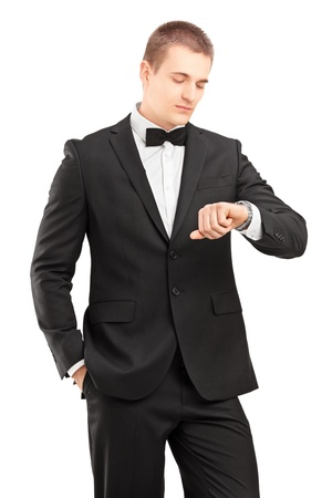man in tuxedo: A young man in black suit with bow tie looking at wrist watch isolated on white background Stock Photo
