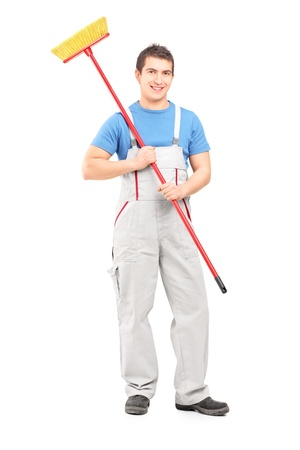 cleaning tools: Full length portrait of a smiling cleaner in a uniform with a broom isolated against white background