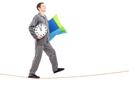 sleepwalking: Full length portrait of a young man with pillow and clock sleepwalking on a rope isolated against white background