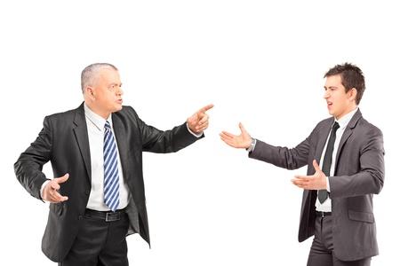 personas discutiendo: Hombre maduro con un traje que tiene una disputa con un joven en ropa formal aislada en el fondo blanco Foto de archivo