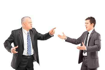 people arguing: Mature man in a suit having a dispute with a young man in formal wear isolated on white background