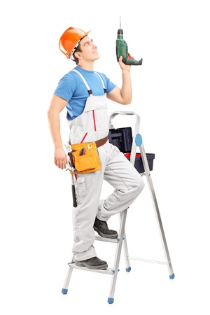 A young worker on a ladder holding a driller isolated on white background photo