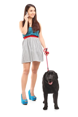 Full length portrait of a female walking her dog and talking on a mobile phone isolated on white background photo