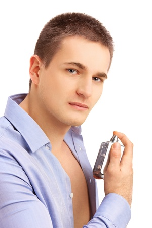 parfume: Portrait of a seductive, handsome young man spraying perfume isolated on white background