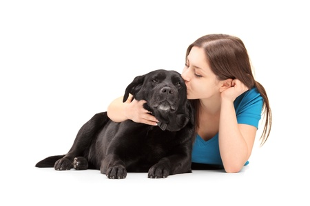 Young female hugging and kissing her dog isolated on white background photo