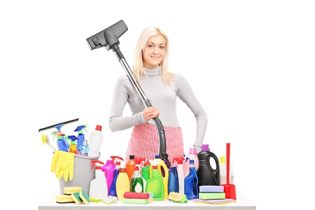 Young smiling woman with a hover and cleaning supplies on a table posing isolated on white background photo
