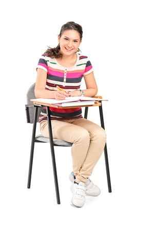 isolated chair: A smiling woman  sitting on a chair and writing down notes isolated on white background Stock Photo