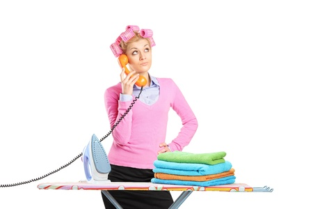 Beautiful young housewife with hair rollers and a telephone standing next to an ironing board isolated on white background photo