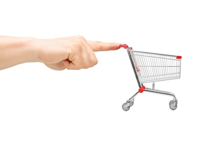 Finger pushing an empty shopping cart, isolated on white background photo