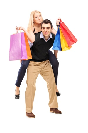 Full length portrait of a young man giving a piggyback ride to a woman with shopping bags isolated on white background photo