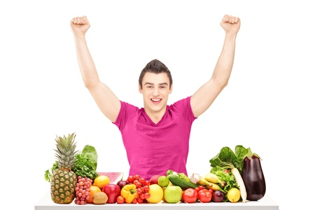 Happy young man raising hands and sitting behind a pile of fruits and vegetables isolated on white background  photo