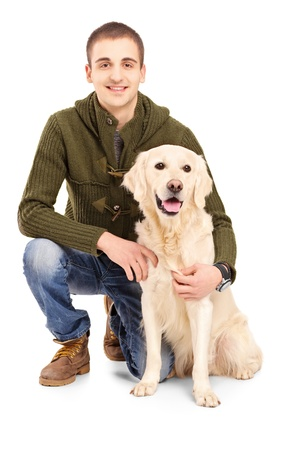 Smiling young man posing with a retriever dog isolated on white background photo