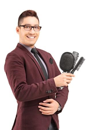 estilista: Joven estilista de cabello masculino la celebración de tres cepillos del pelo, aislados en fondo blanco